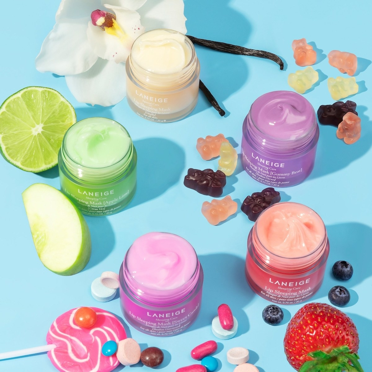 Laneige sleeping mask in a variety of scents styled on a table with fruits and candies