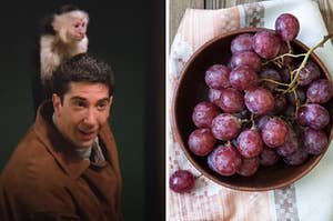 A man is holding a monkey on his shoulder with a bowl of grapes on the right