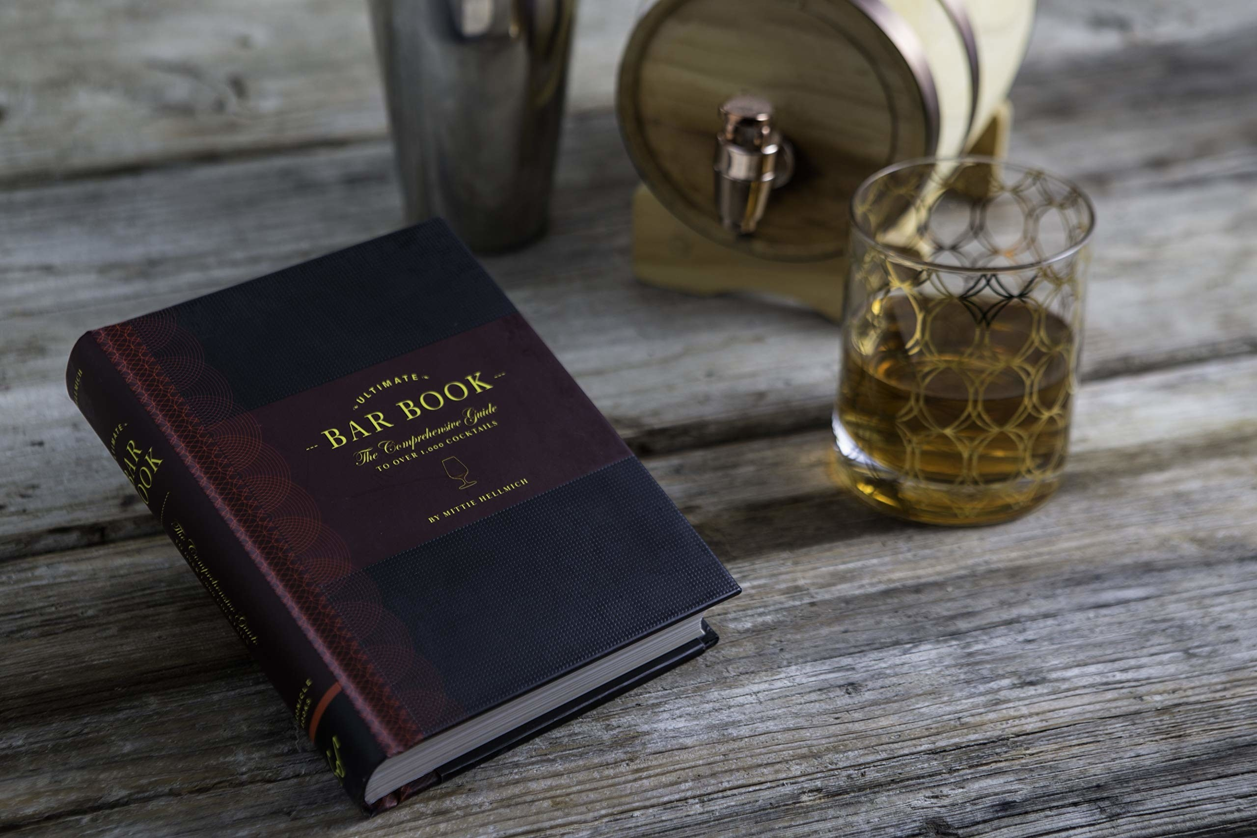 """The Bar Book"" styled on a table with a whiskey barrel, shaker, and cocktail"