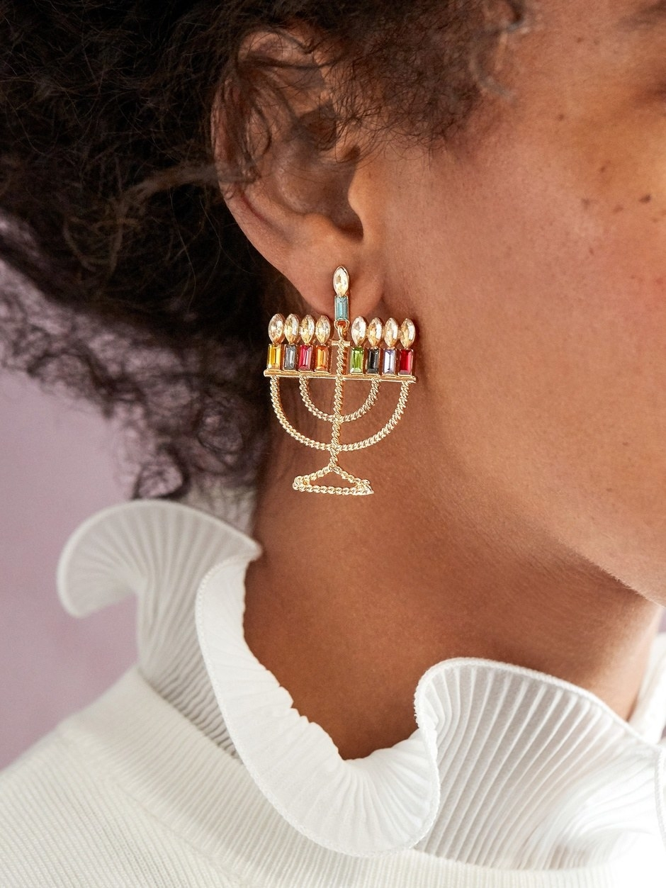 A model wearing the gold menorah with colorful jeweled candles earrings