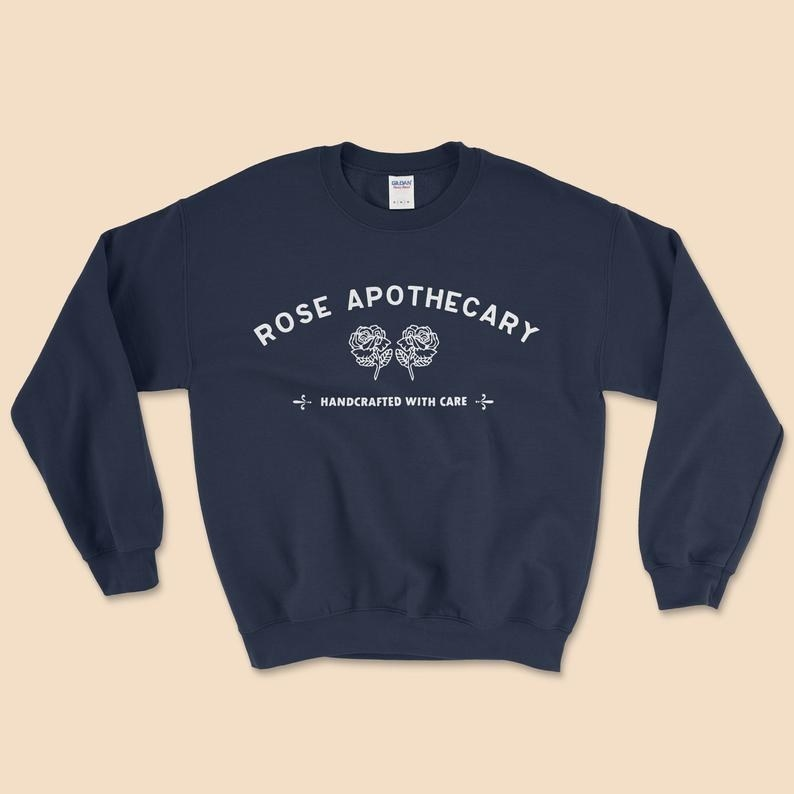 "The black sweatshirt with the Rose Apothecary name and logo and motto ""Handcrafted with care"""
