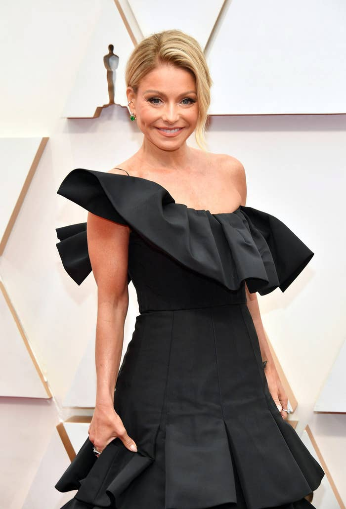 Kelly Ripa in a dark, off the shoulder ruffled black dress