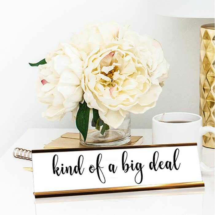 "a brass and white desk plate that says ""kind of a big deal"""