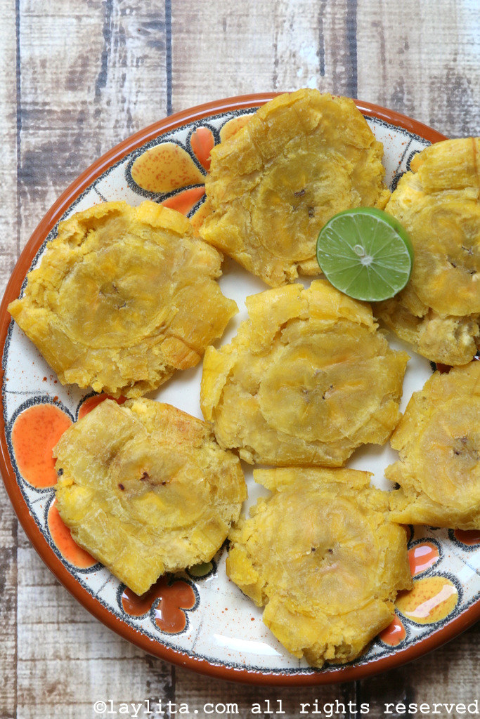 A plate of tostones garnished with fresh lime.