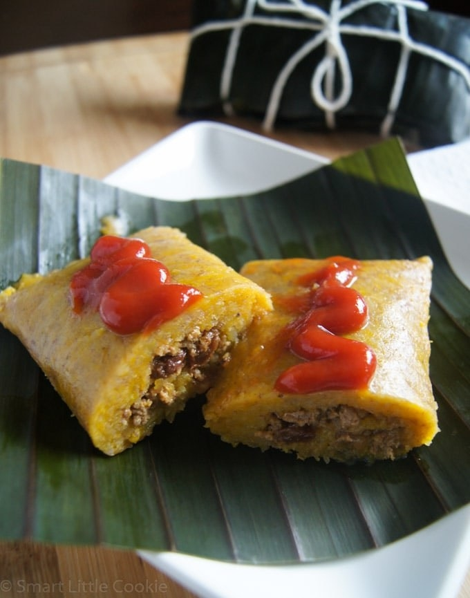 A plate of pasteles en hoja with sauce on top.