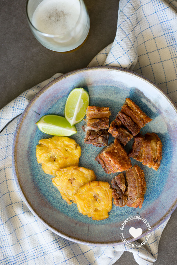 Chicharrón plated with tostones and fresh lime.