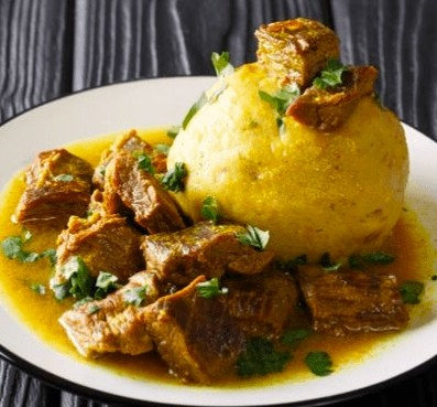A plate of mofongo garnished with fresh herbs.