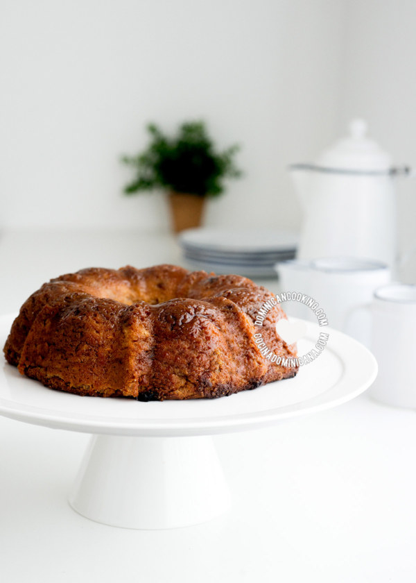 A fresh loaf of pudín de pan on a cake stand.