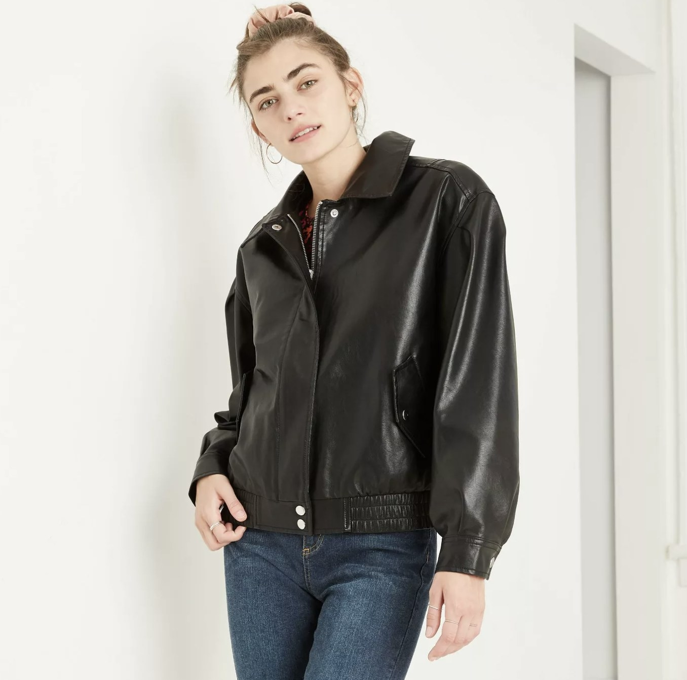 Model wears faux leather bomber jacket with jeans