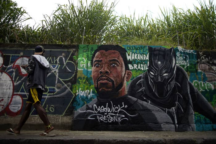 A passer-by looks at a mural painting in honor of the late actor Chadwick Boseman