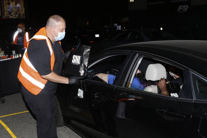 """People in a car getting an """"SNL"""" bag from someone wearing a mask"""