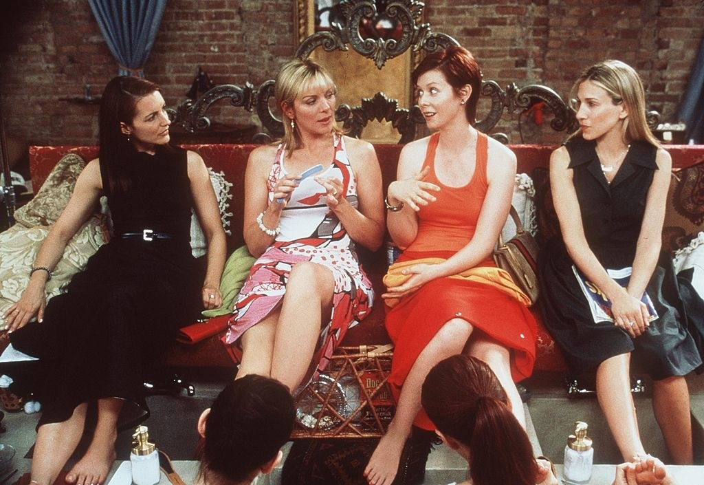 "Kristin Davis, Kim Cattrall, Cynthia Nixon and Sarah Jessica Parker sitting on a couch in ""Sex and the City"""