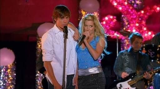 Troy and Sharpay on stage singing together while Troy looks disinterested