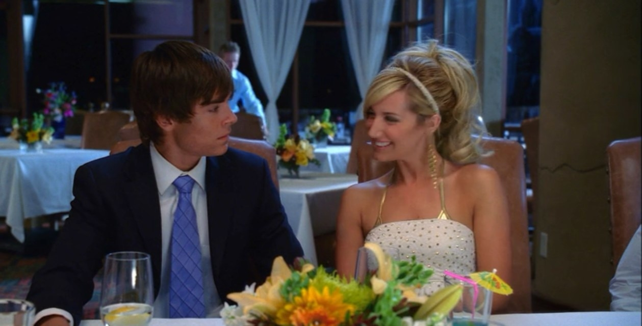 Sharpay smiling at Troy at a fancy dinner party and he looks uncomfortable
