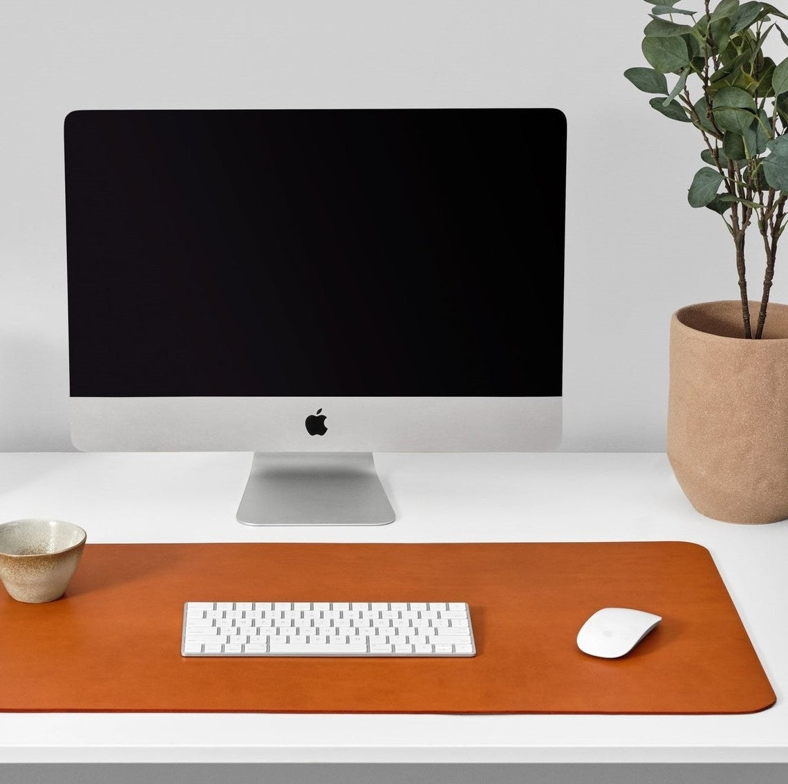 A keyboard, mouse, and bowl on top of the leather desk mat