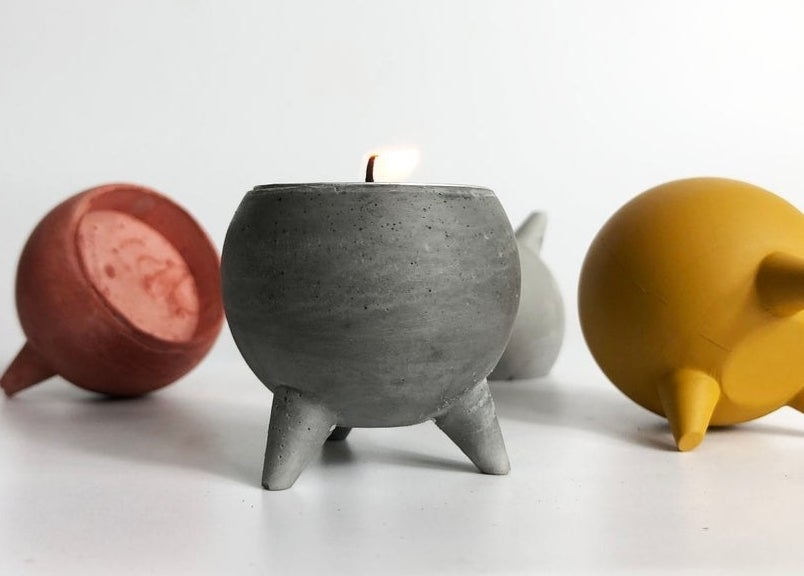 Four tea light holders on a table, one has a candle inside