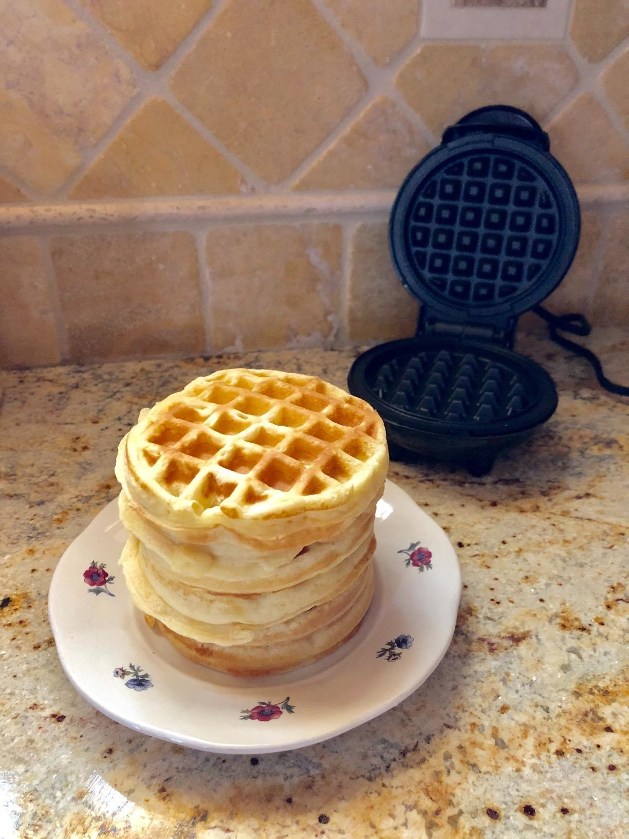 Stack of waffles, which are about the size of Eggo waffles, next to the waffle maker