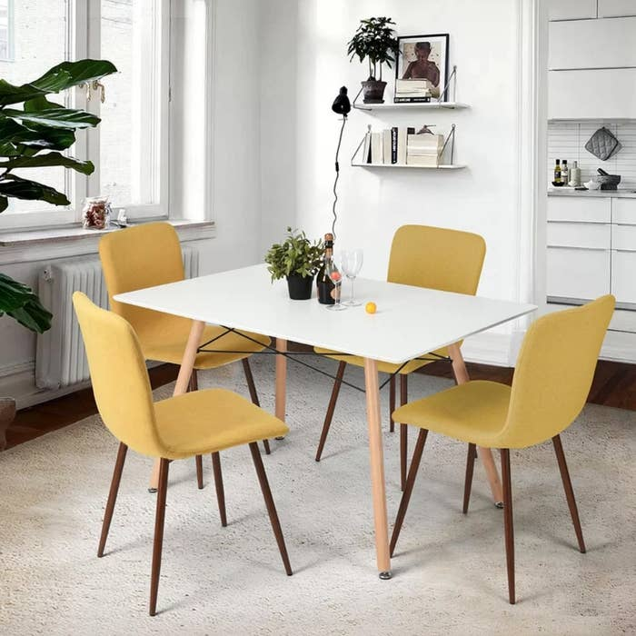 The upholstered chairs in yellow positioned around a white dining table