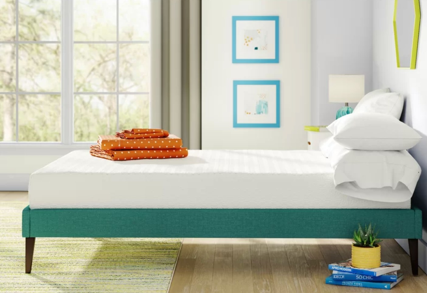 The memory foam mattress sitting atop a bed frame with folded linens at the end of the bed