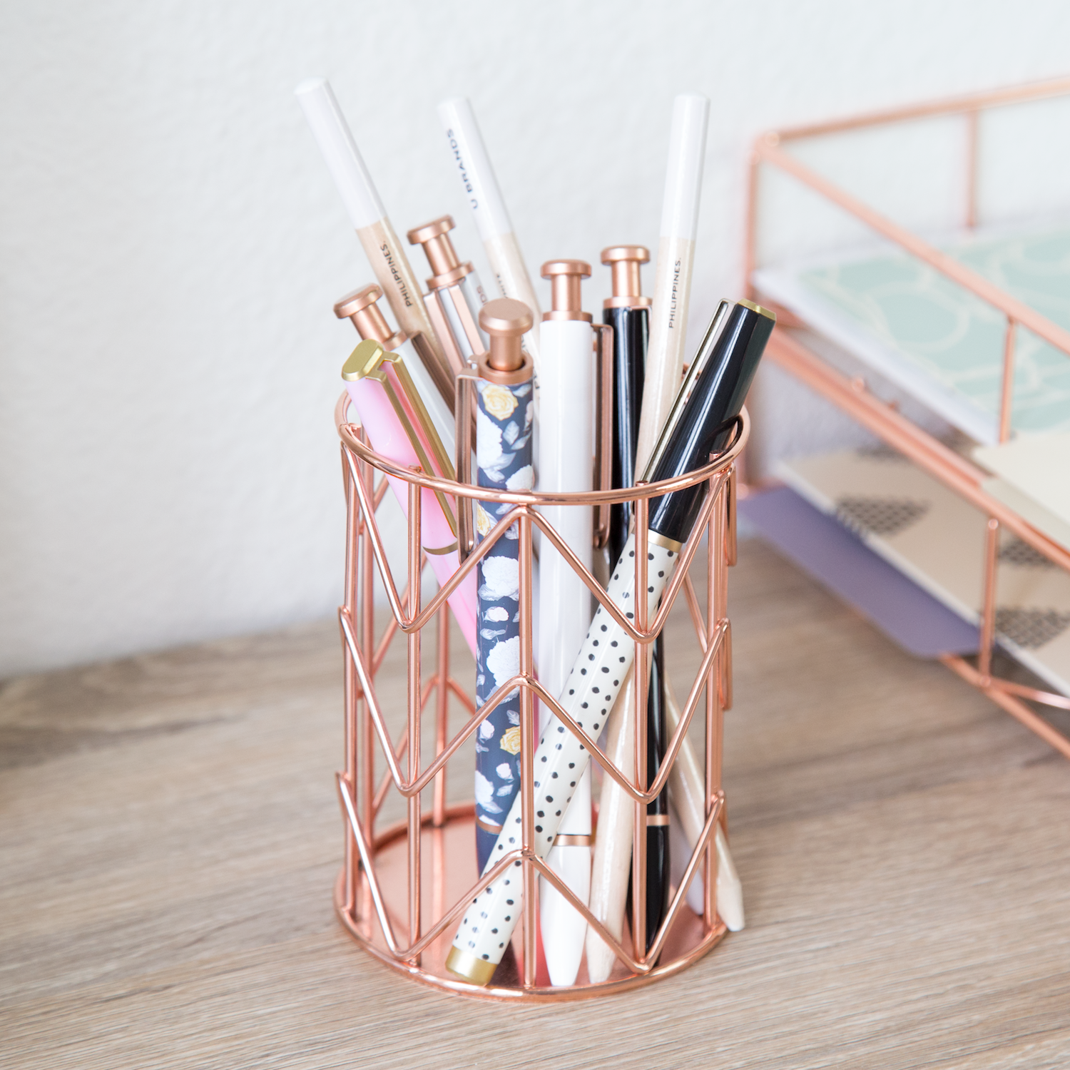 An open rose gold pencil cup with pencils in it