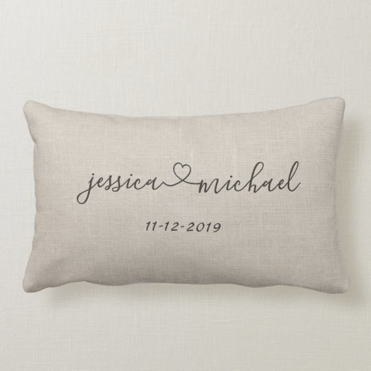 a tan lumbar pillow with jessica heart sign michael on it and a date beneath the script