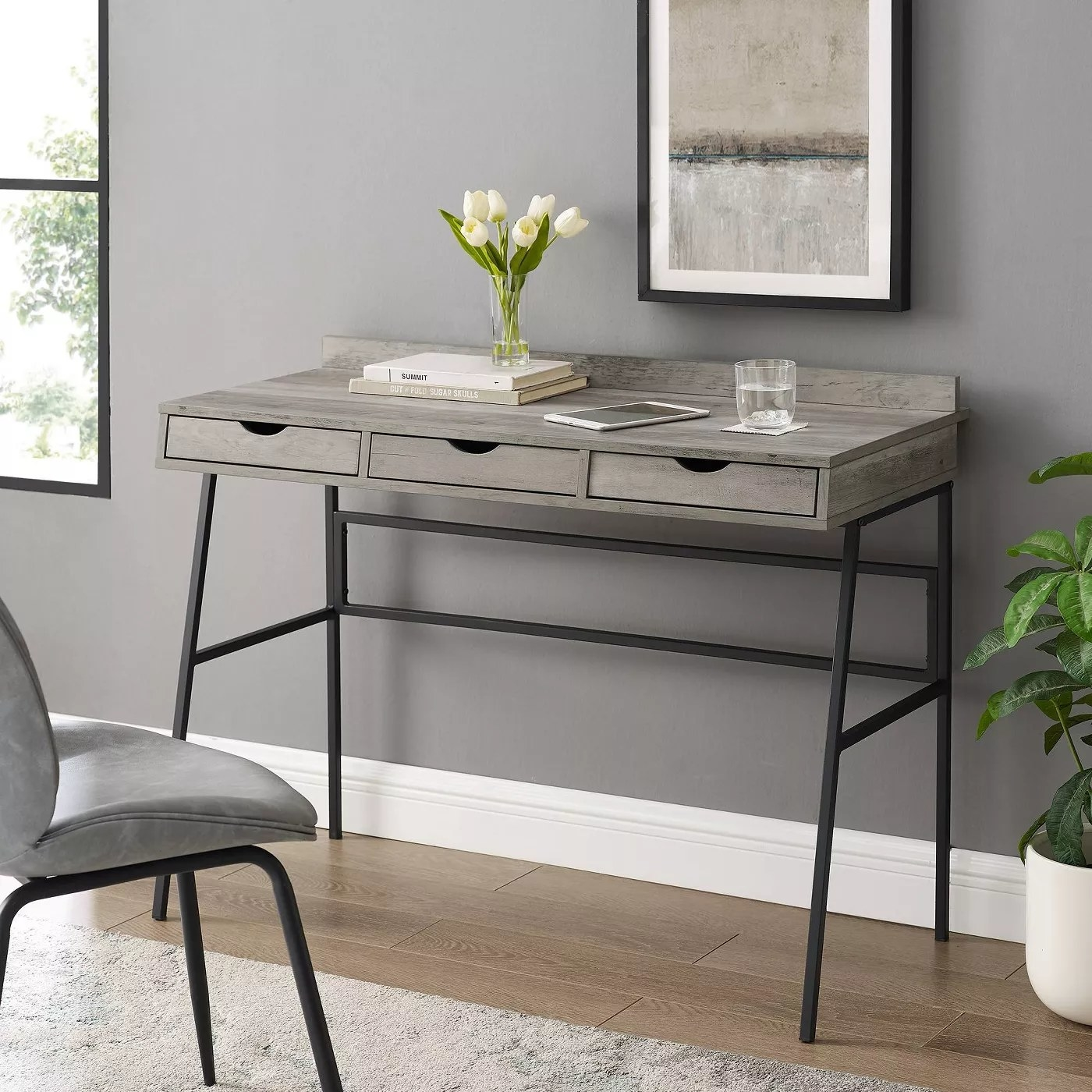 A gray writing desk with three drawers and a black steel frame