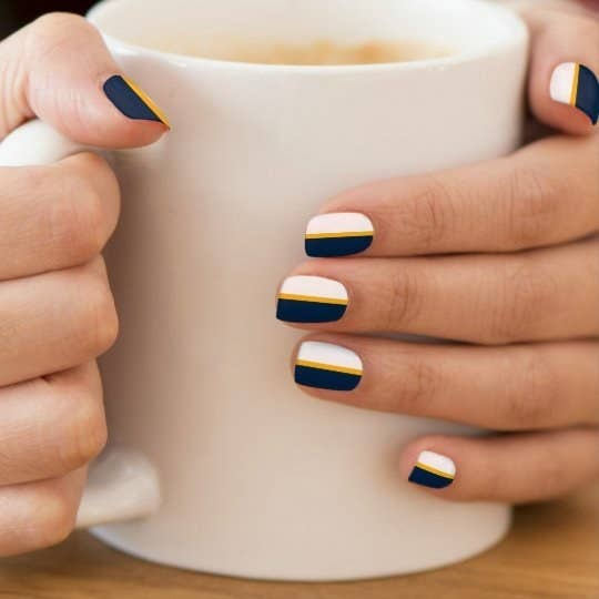 a model holding a mug with nails that feature stripes of blue gold and white