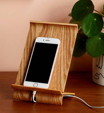 The curved wooden mount holding a cell phone on a desk