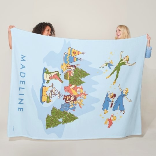 two models holding up a light blue blanket with peter pan characters on it