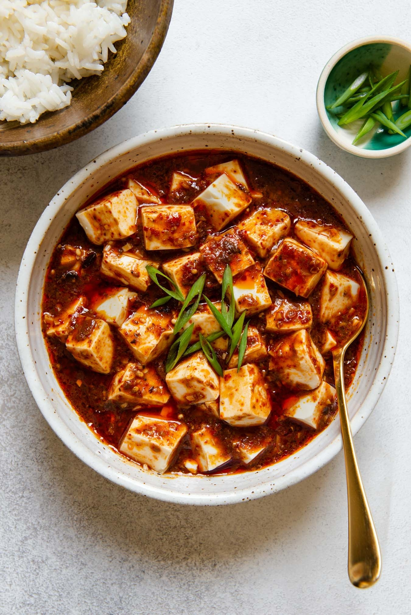 A bowl of tofu cubes in a spicy red sauce with scallions on top.
