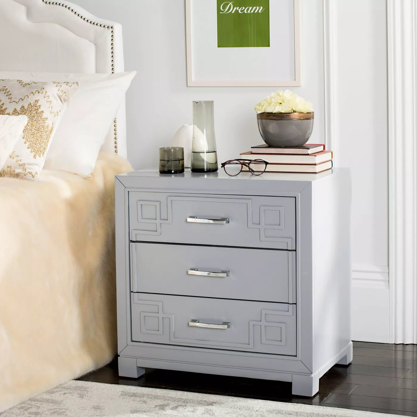 A gray side table with three drawers, silver handles, and a Greek key pattern