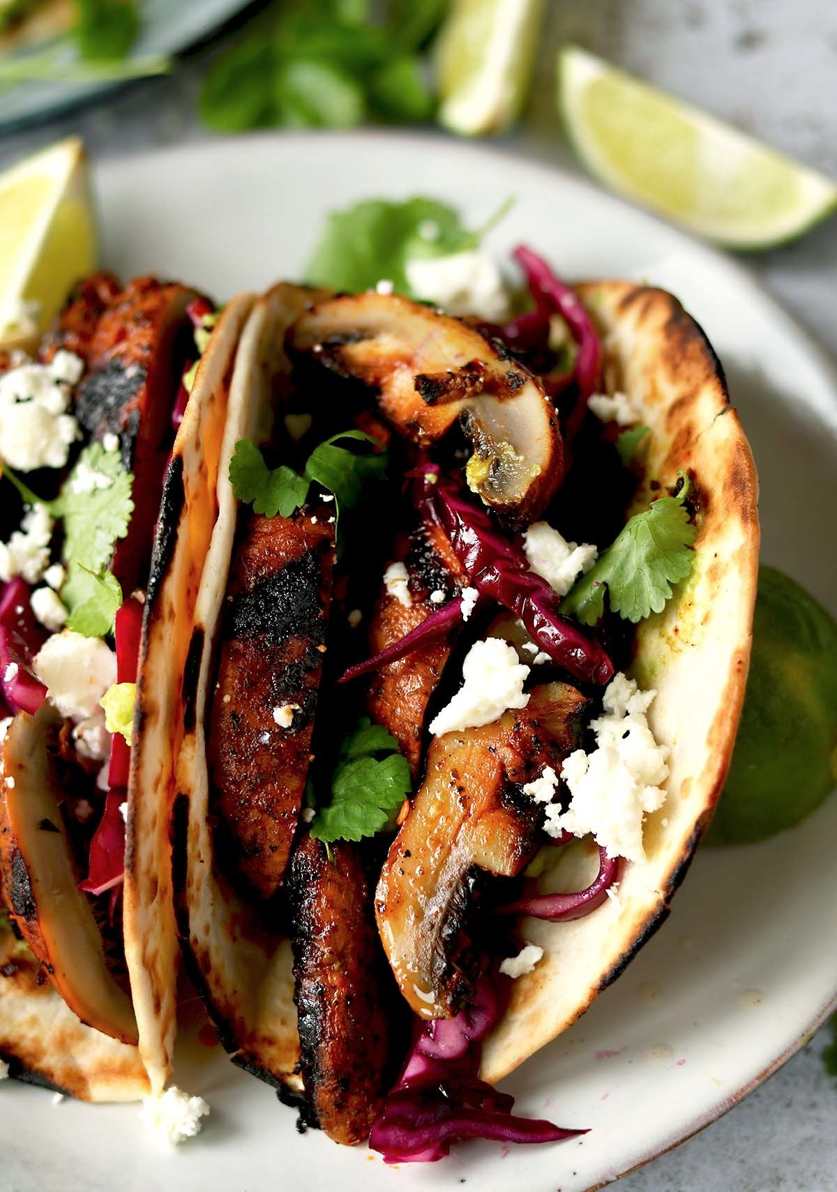 Two tacos filled with sliced mushrooms, cabbage, herbs, and cotija cheese.