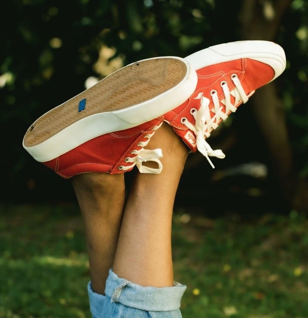 A person wearing Keds with jeans on a lawn