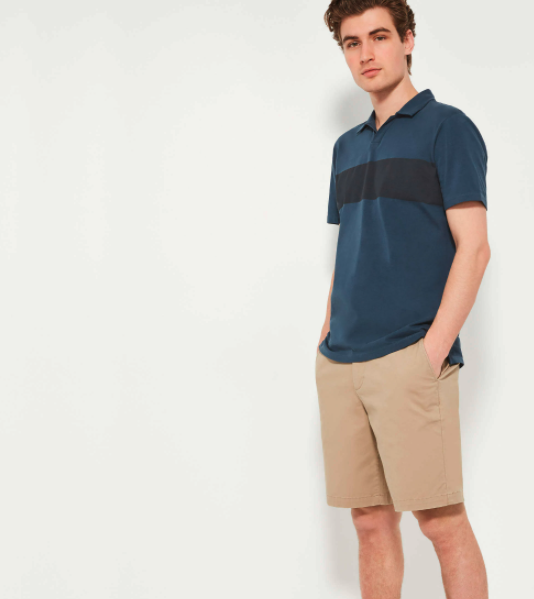 A model wears a dark blue polo shirt with a thick black stripe across the chest
