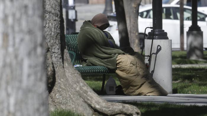 A person experiencing homelessness is wrapped in a blanket on a bench