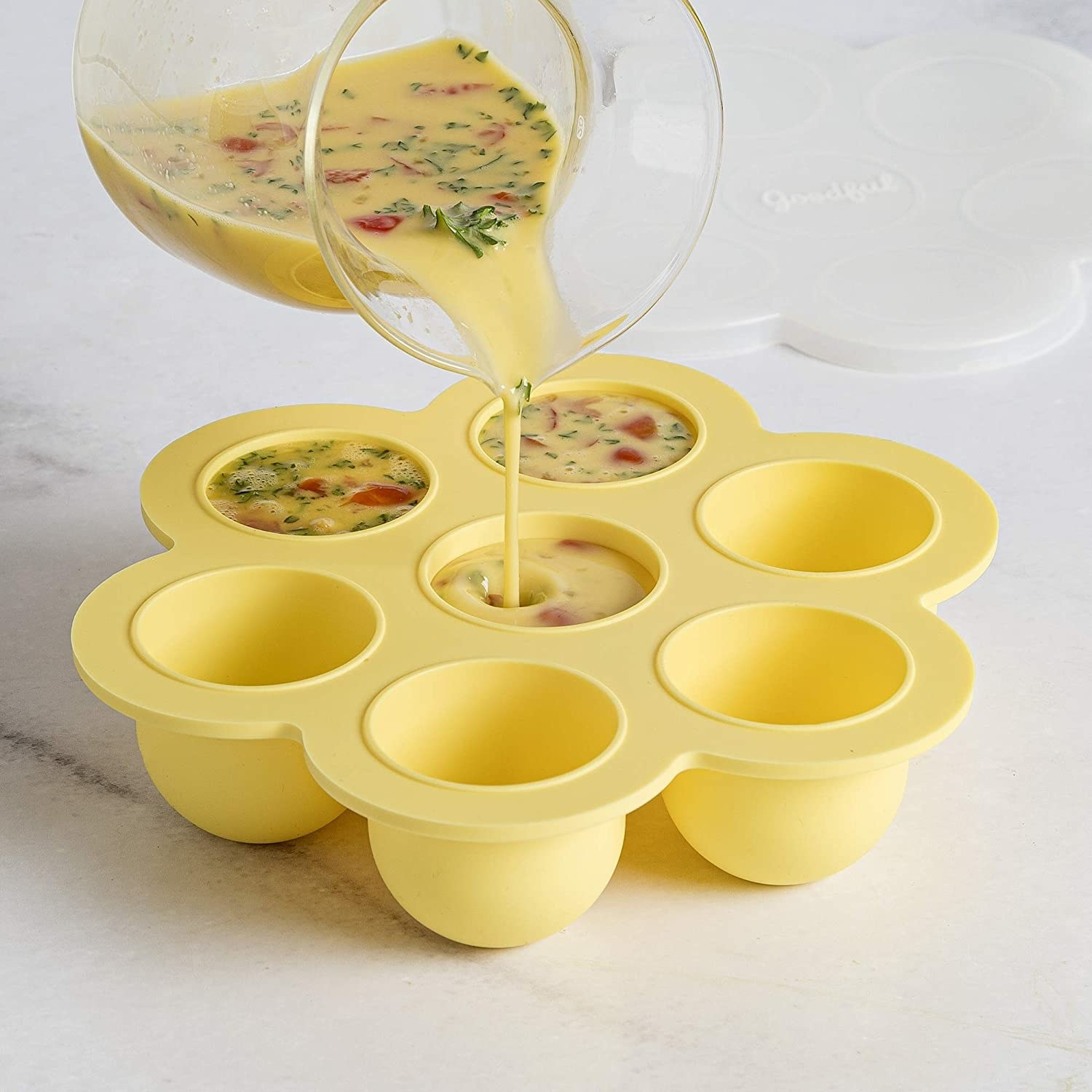 Mixture of eggs and other ingredients being poured into the mold to make egg bites