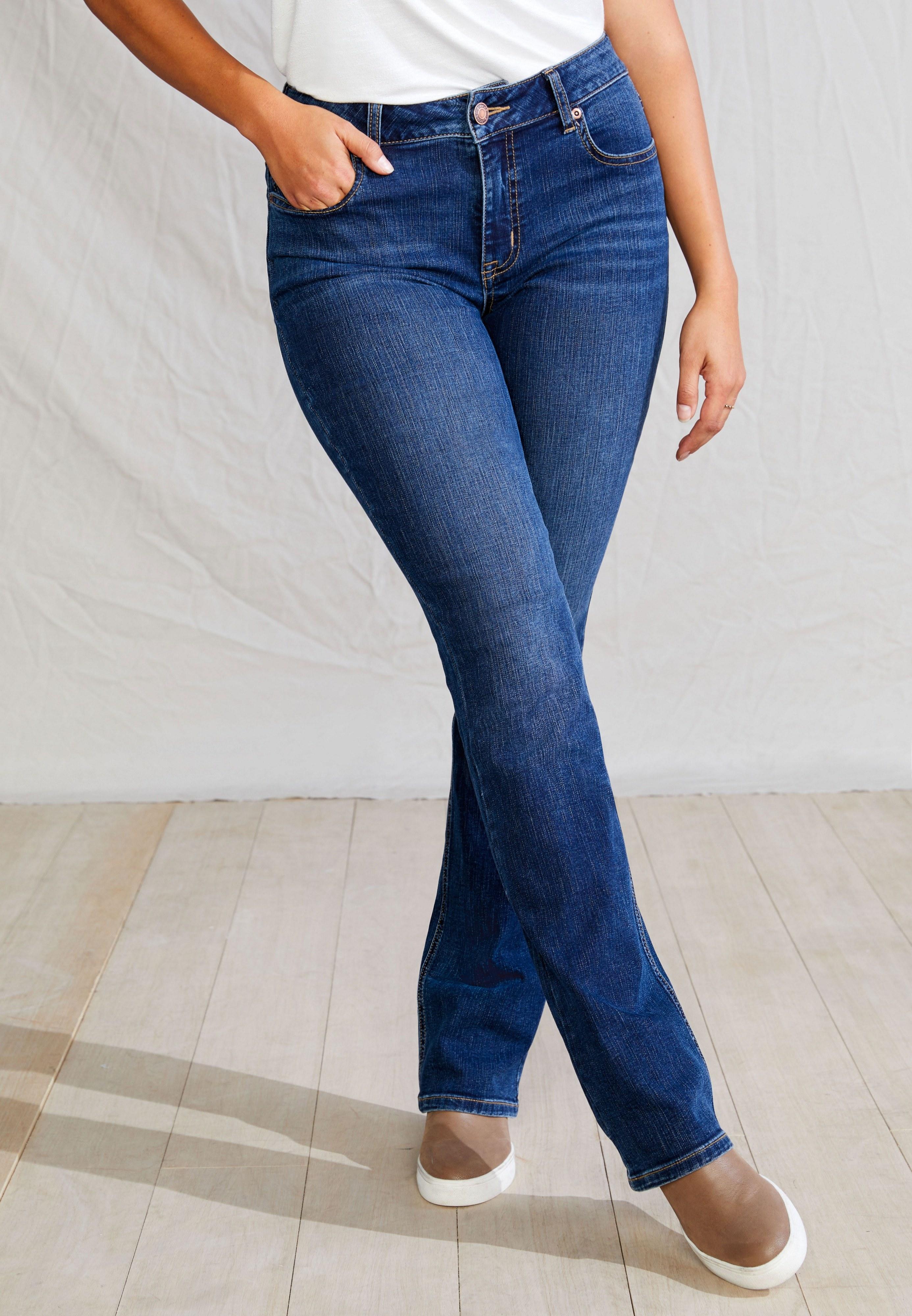 Model wearing a dark wash slim boot pair