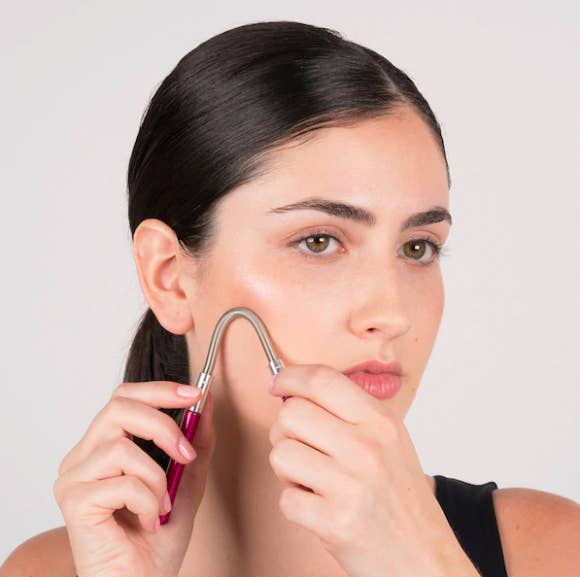 A person using the coil tool to remove hair from their cheek