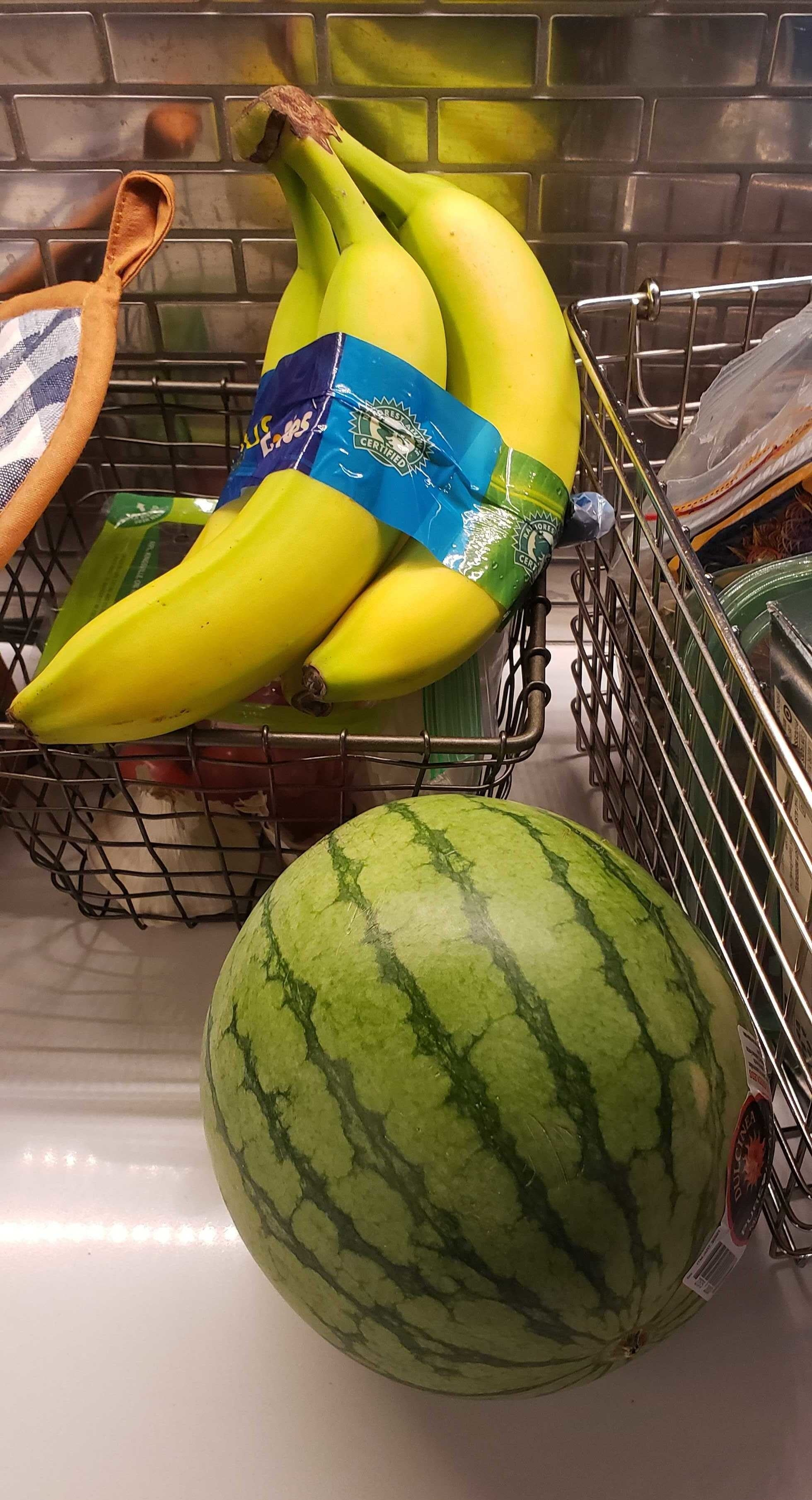 Bunch of bananas sitting in a basket and a small watermelon on the counter