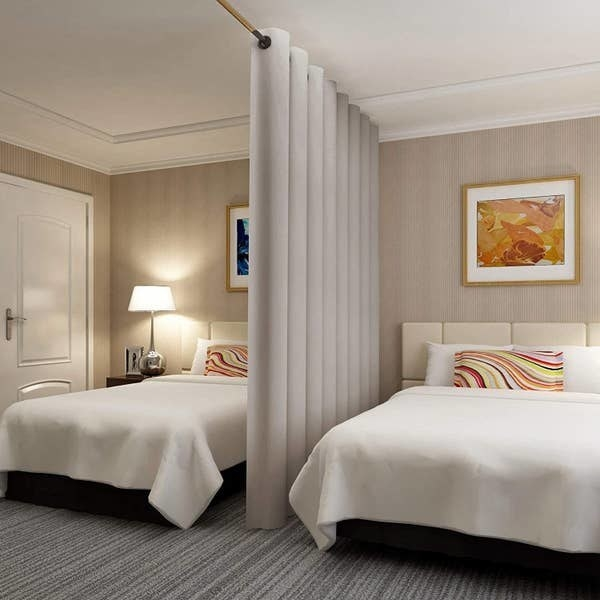 A photo of the room divider curtain separating two beds in a hotel room