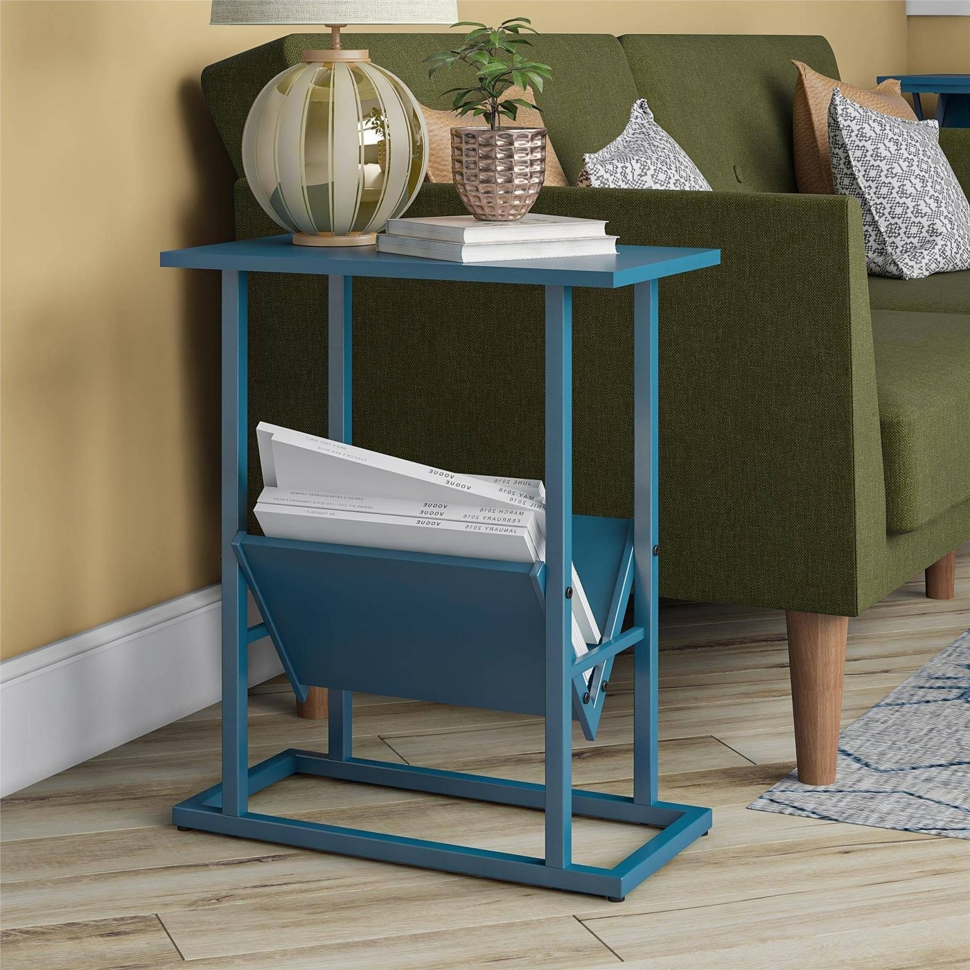 blue end table with white magazines on the bottom