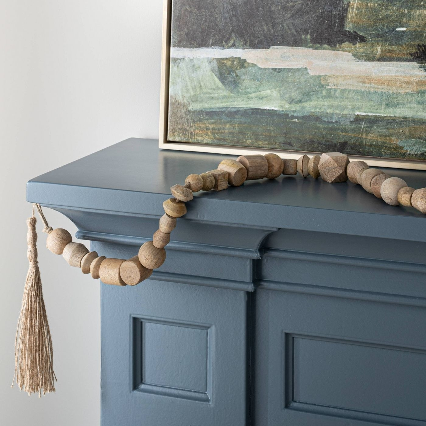 wooden bead garland decorating a dark blue fireplace mantle