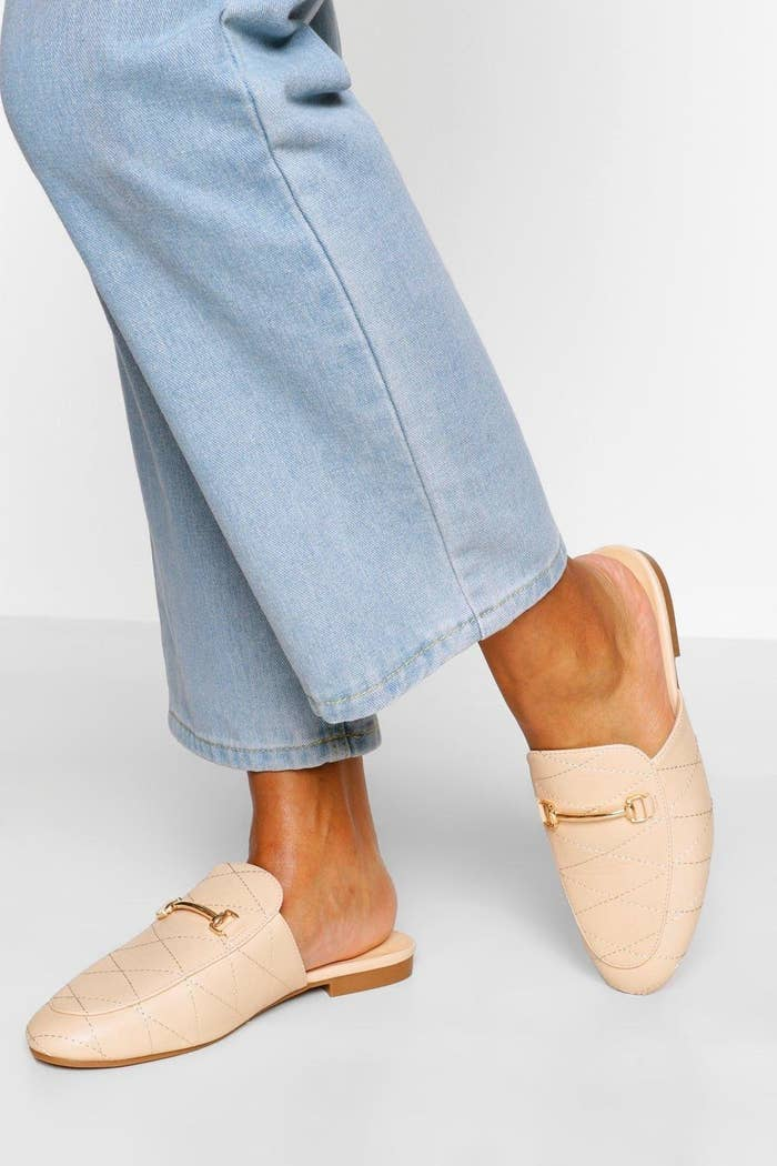 Model wears cream colored quilted mules with a gold band on the front and light wash jeans
