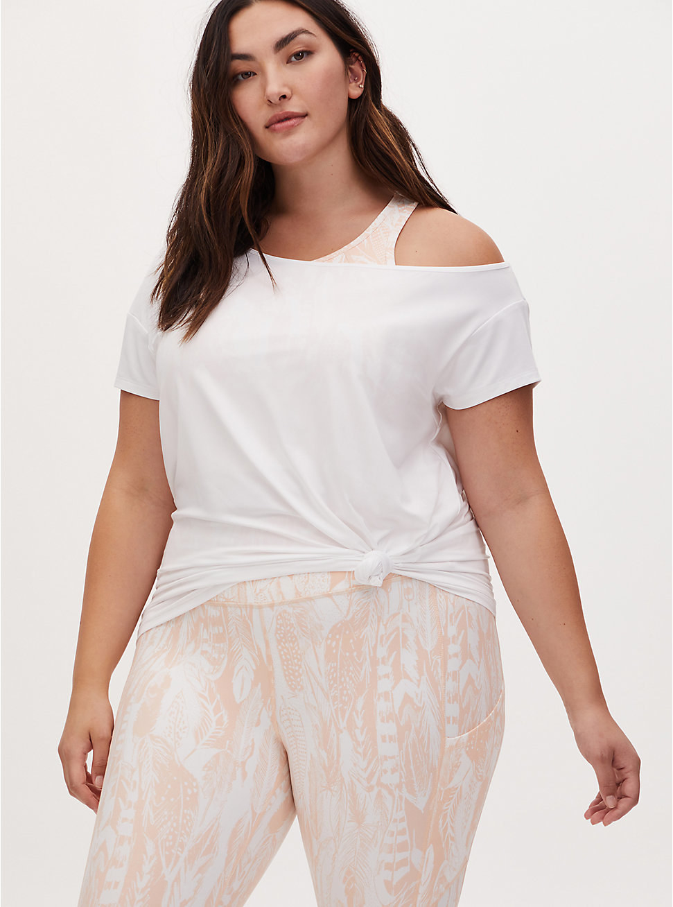 Model wears white off-shoulder short sleeve tee with white and light pink leggings