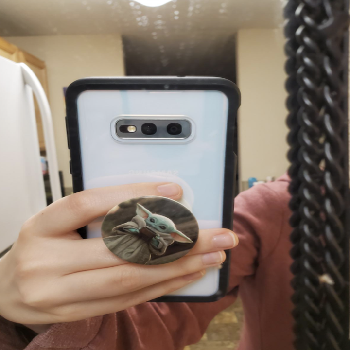a reviewer holding their phone with their popsocket that features an image of baby yoda drinking soup on it