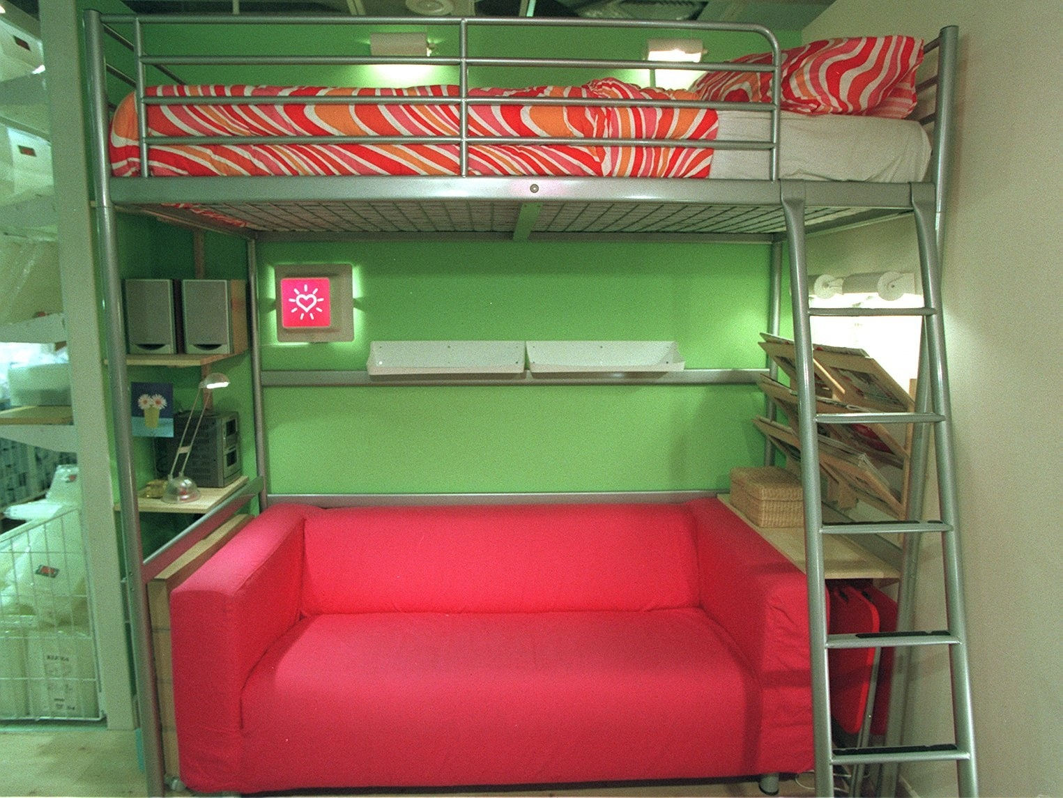 An Ikea metal loft bed set up with a pink couch on the bottom of it