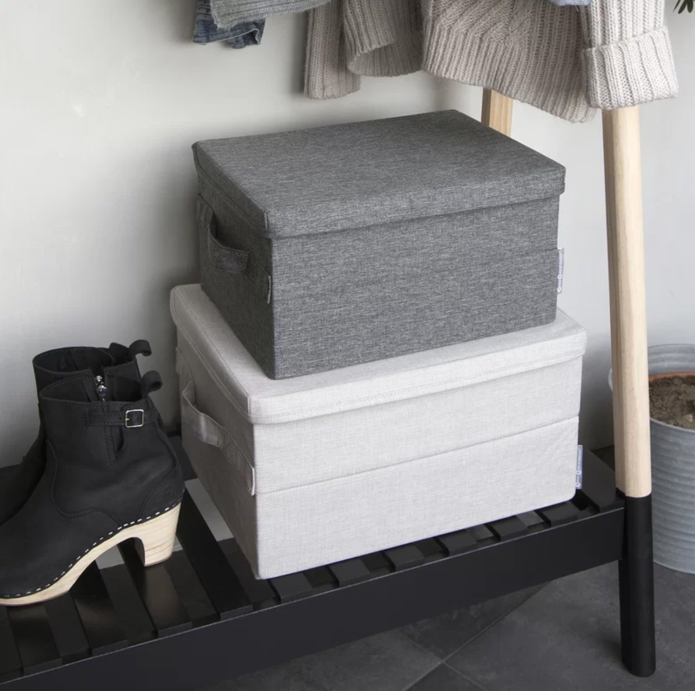 The storage boxes in light and dark gray on a rack in the closet