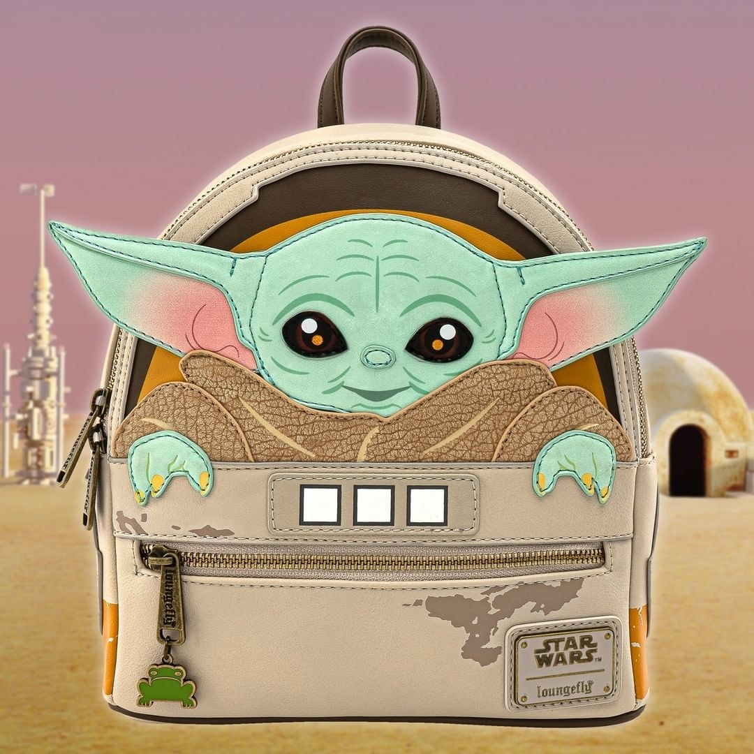 a backpack designed to look like baby yoda is sitting in the back of it
