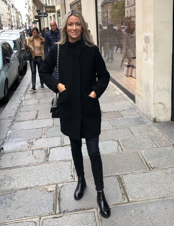 reviewer wearing black midi coat