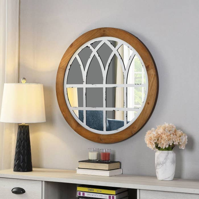wooden framed circular mirror with white rustic design on top